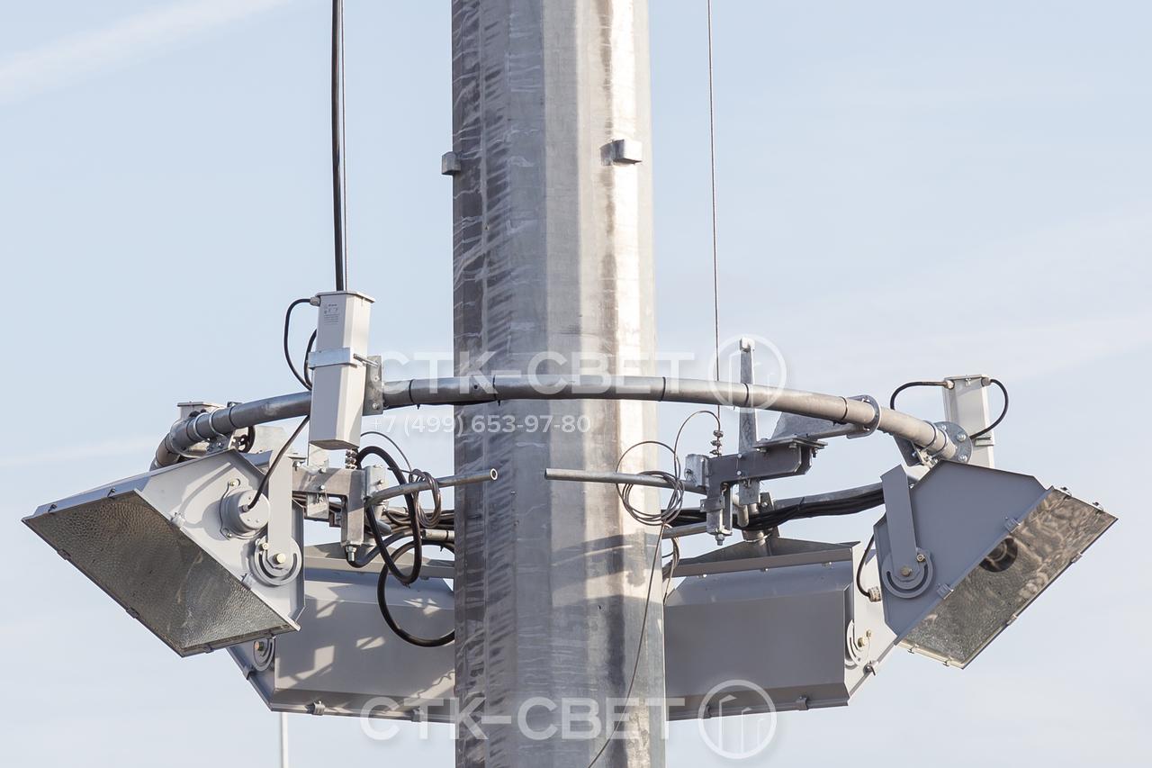 На фото изображена спускаемая корона мачты. Она подвешивается на тросах, которые проходят от лебедки внутри полого ствола. Благодаря этому в рабочем состоянии элементы подъемного механизма не видны и не портят дизайн конструкции.