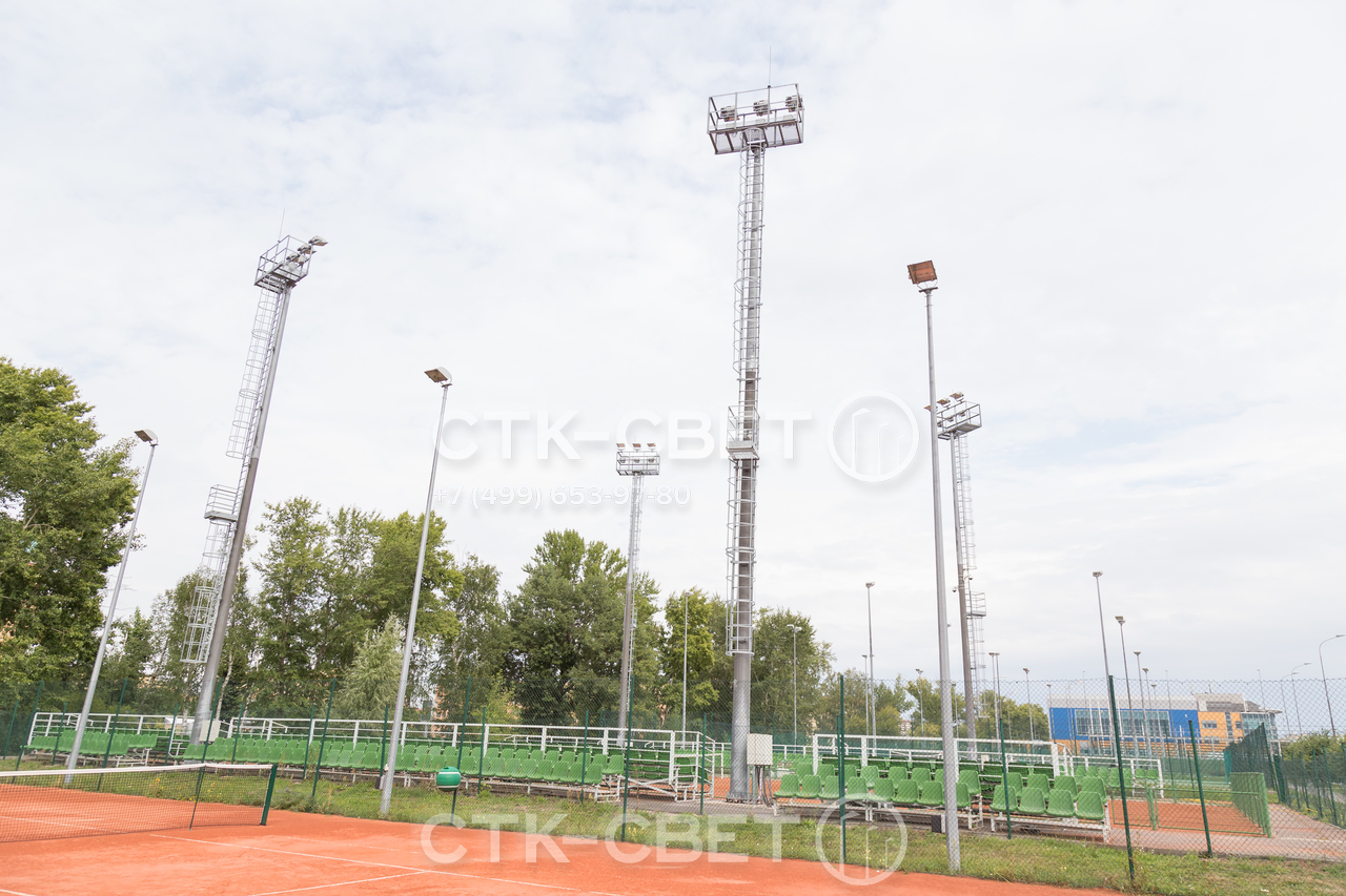 На фото изображены мачты со стационарной короной, которые используются для освещения теннисных кортов. Доля их обслуживания не нужно использовать АГП, которые не смогут подъехать к нужному месту, не испортив корт.