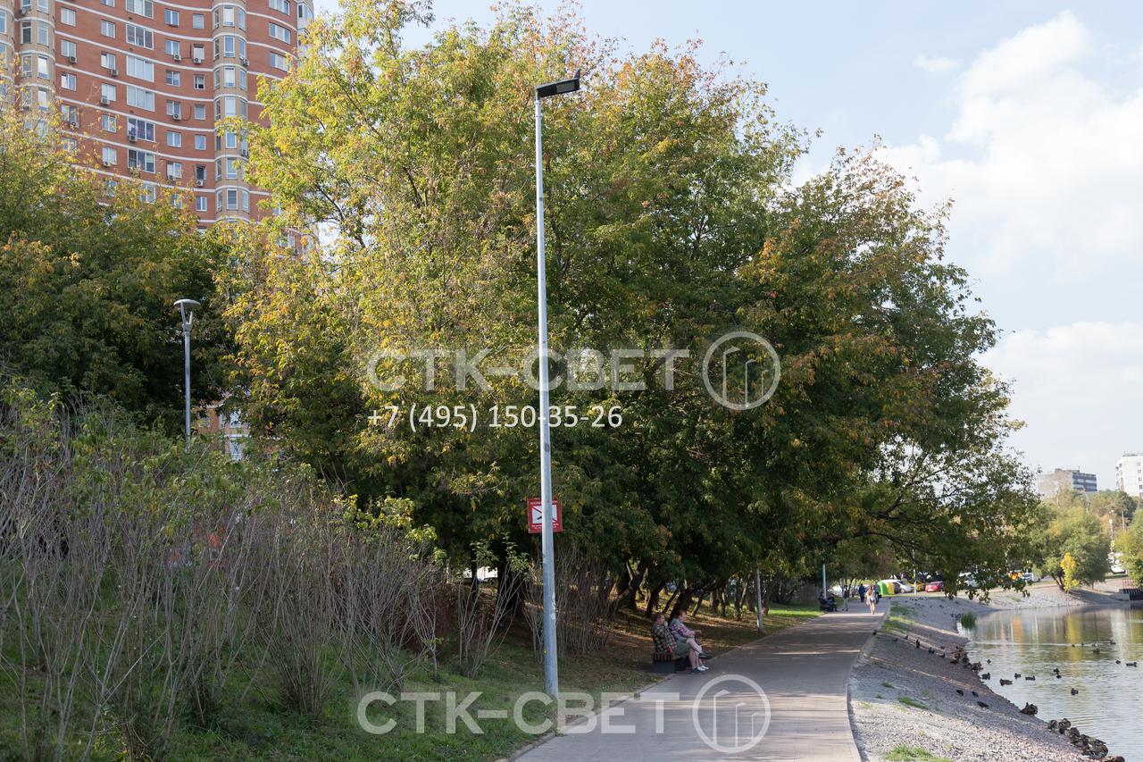 Несиловые опоры из листовой стали с граненым стволом стоят недорого и часто используются для освещения придомовой территории. В варианте на фото на оголовок установлен светодиодный светильник без кронштейна.