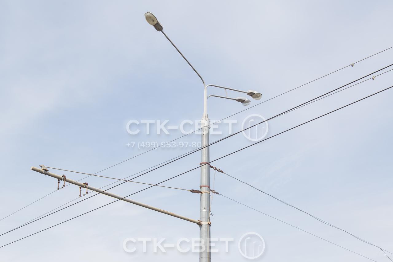 Силовые опоры для контактной сети имеют очень большую несущую способность. На изображенном стволе установлены одновременно кронштейн с тремя светильниками, растяжки для рекламных конструкций, консоль для троллейбусных проводов.