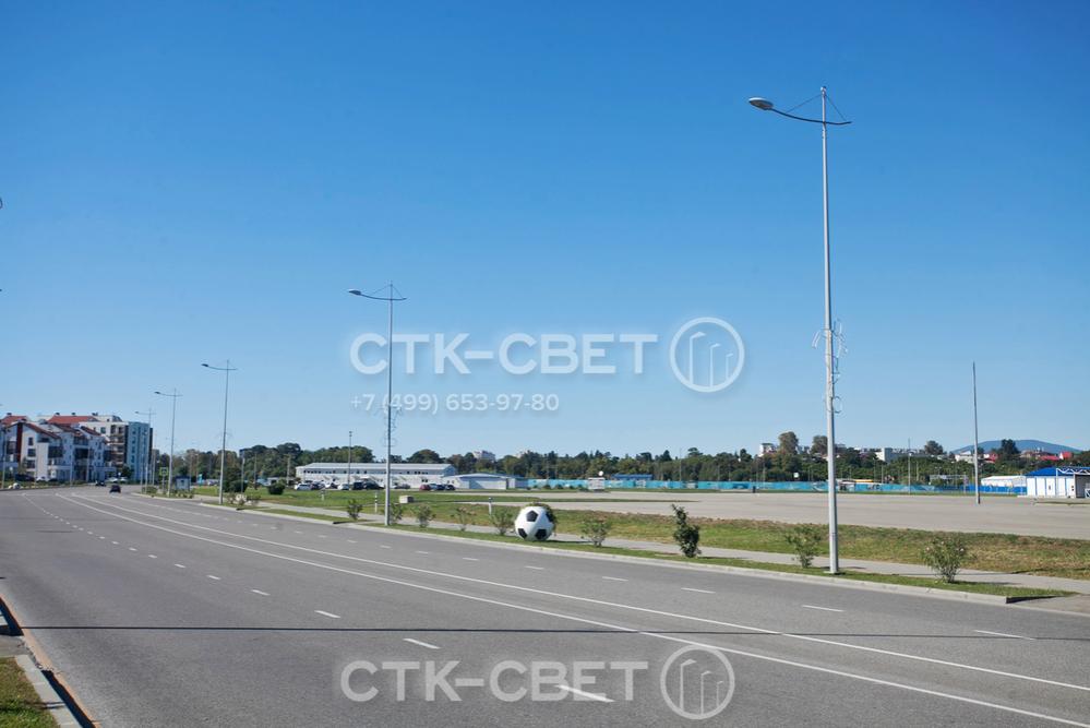 На фото изображены граненые опоры, с помощью которых освещается автомобильная дорога. Для украшения объекта на оголовках установлены декоративные кронштейны, а на стволе закреплены украшения со светодиодными лентами.