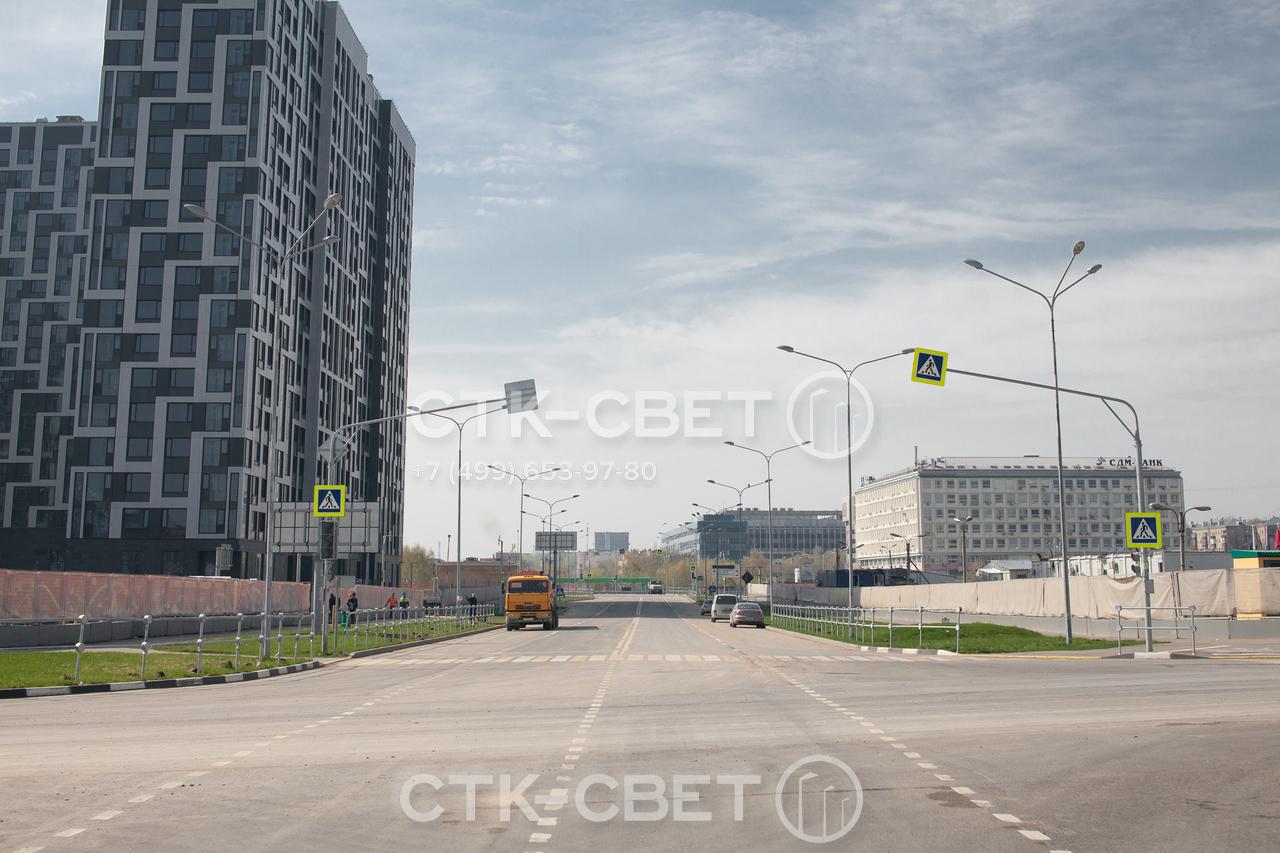 Осветительные опоры, изображенные на фото, используются для освещения автомобильной магистрали. На оголовках установлены трехрожковые светильники, которые создают заливающее освещение вокруг ствола опоры.