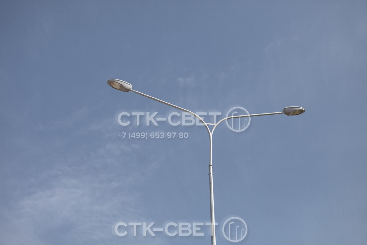 На фото изображена опора с кронштейном под 2 консольных светильника. Использование двух световых приборов позволяет осветить пространство по обе стороны от ствола. Например, проезжую часть для автомобилей и тротуар.