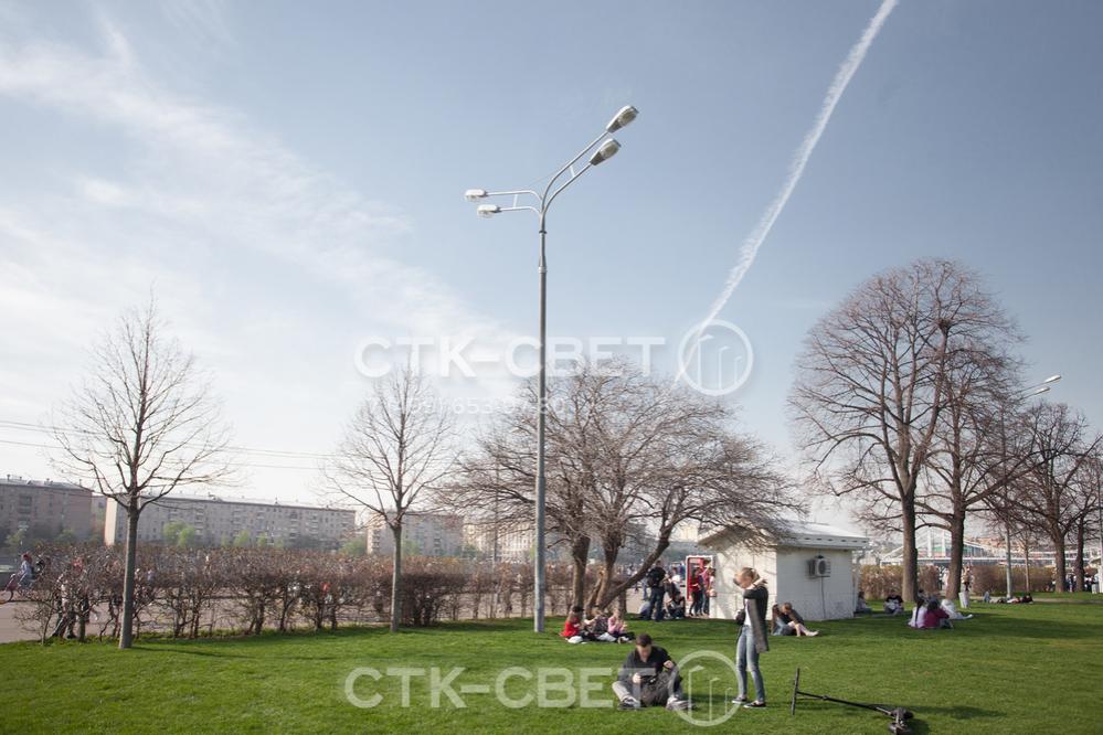 Изображенная на фото опора имеет круглое поперечное сечение ствола, поэтому красиво смотрится в парке. Чтобы создать заливающее освещение вокруг ствола на оголовок установлен кронштейн с четырьмя рожками и светильниками.