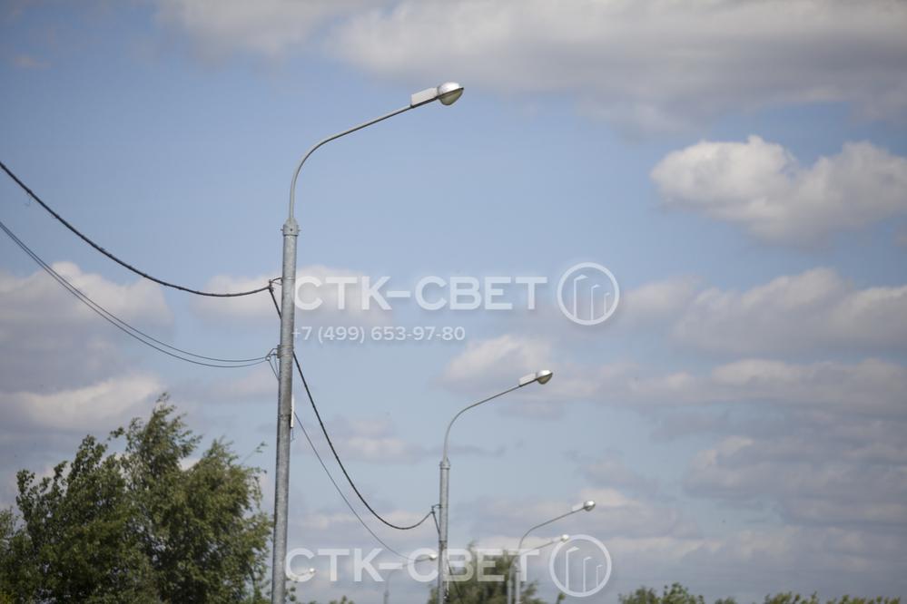 На фото изображены силовые осветительные опоры, которые оснащены консольными светильниками с газоразрядными лампами. Силовые линии подвешены на стволе с помощью отдельной арматуры.