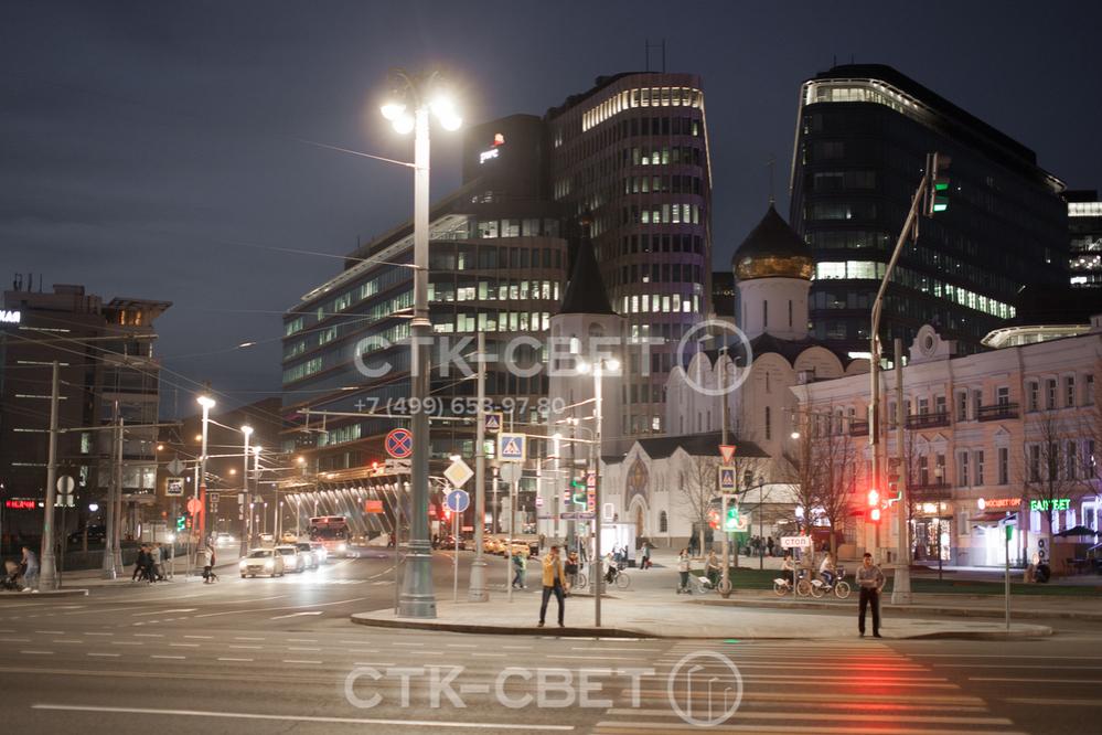 На опору с круглым стволом можно установить декоративный кронштейн под светильники, как изображено на фото. Благодаря этому конструкция будет не просто выполнять утилитарную задачу, но и украшать улицу населенного пункта.