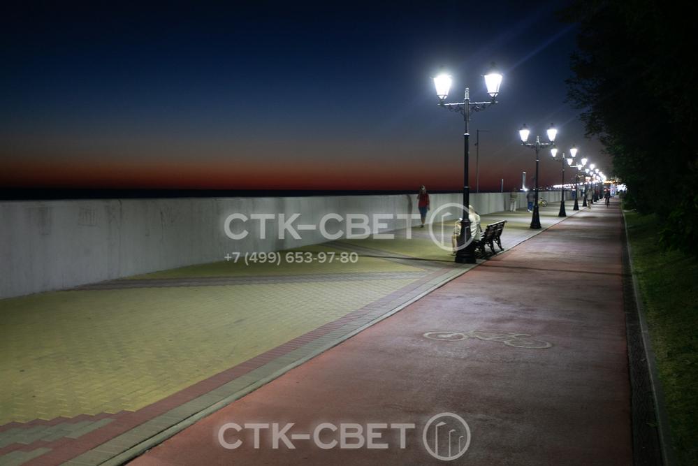 На фото представлена система освещения набережной на основе осветительных комплексов. На их верхушке установлены по два светильника, за счет чего одновременно освещается и тротуар, и велосипедная дорожка.