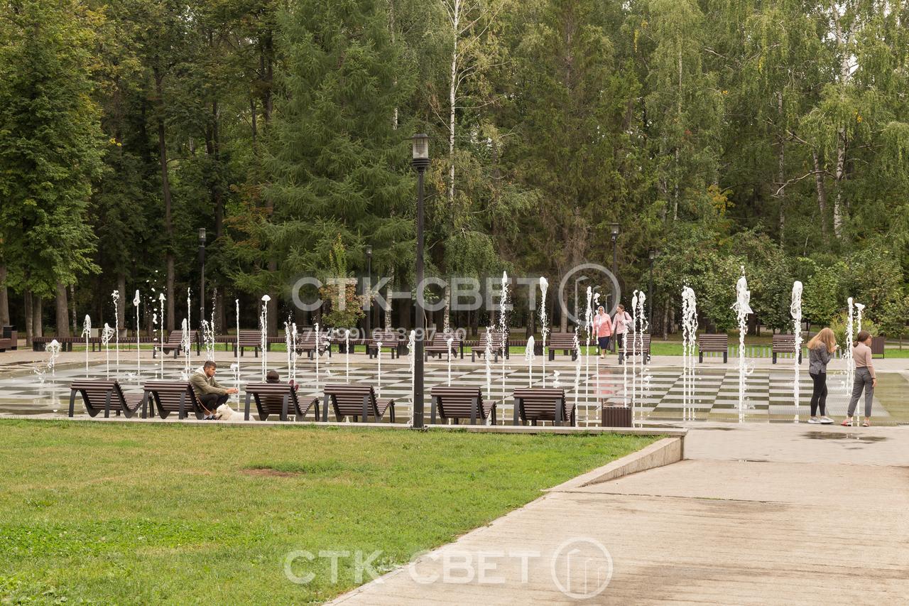 На фото изображены осветительные опоры, установленные в парке. Благодаря черной окраске корпуса они органично сочетаются с коваными элементами скамеек, ограждением. Не выделяются на фоне окружающей растительности.