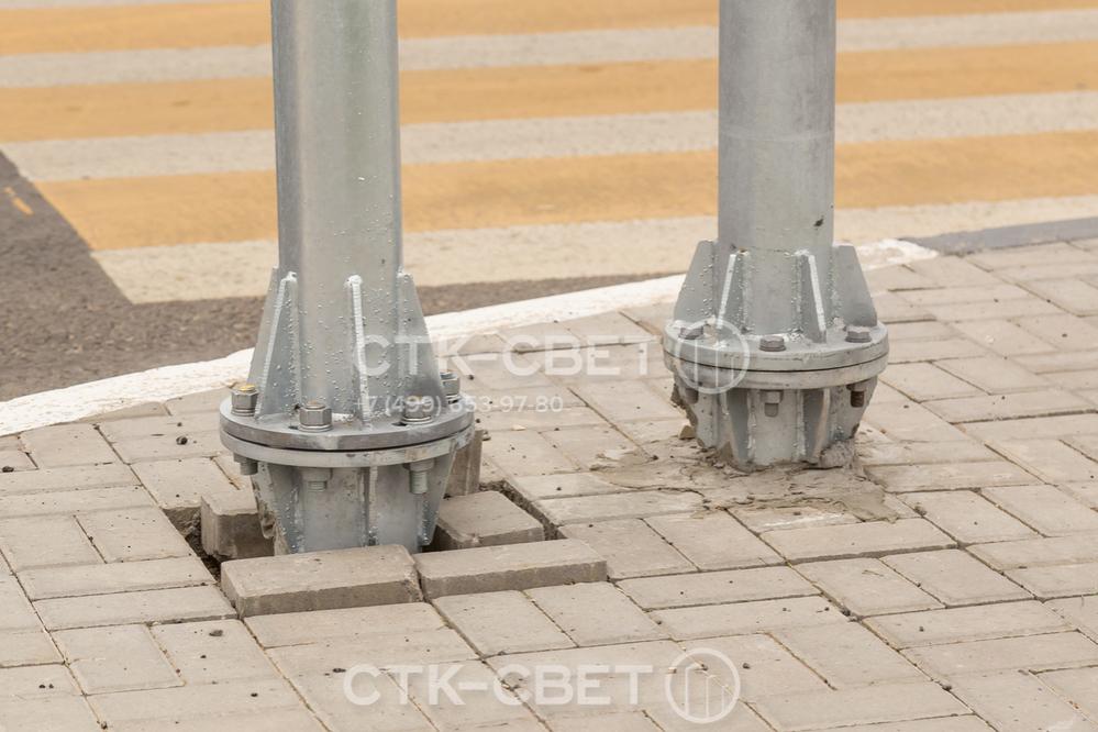 На фото изображен фланец, с помощью которого производится монтаж светофорной опоры на месте. Подпятник круглой формы дополнительно укреплен с помощью треугольных косынок, которые увеличивают надежность конструкции.