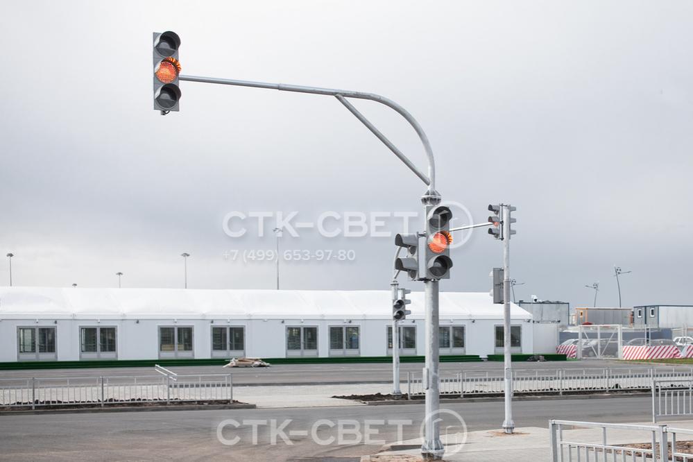 Светофорная опора, представленная на фото, используется для крепления двух светофоров. Она монтируется на месте с помощью фланца, для чего необходимо заранее приобрести и забетонировать закладной элемент.