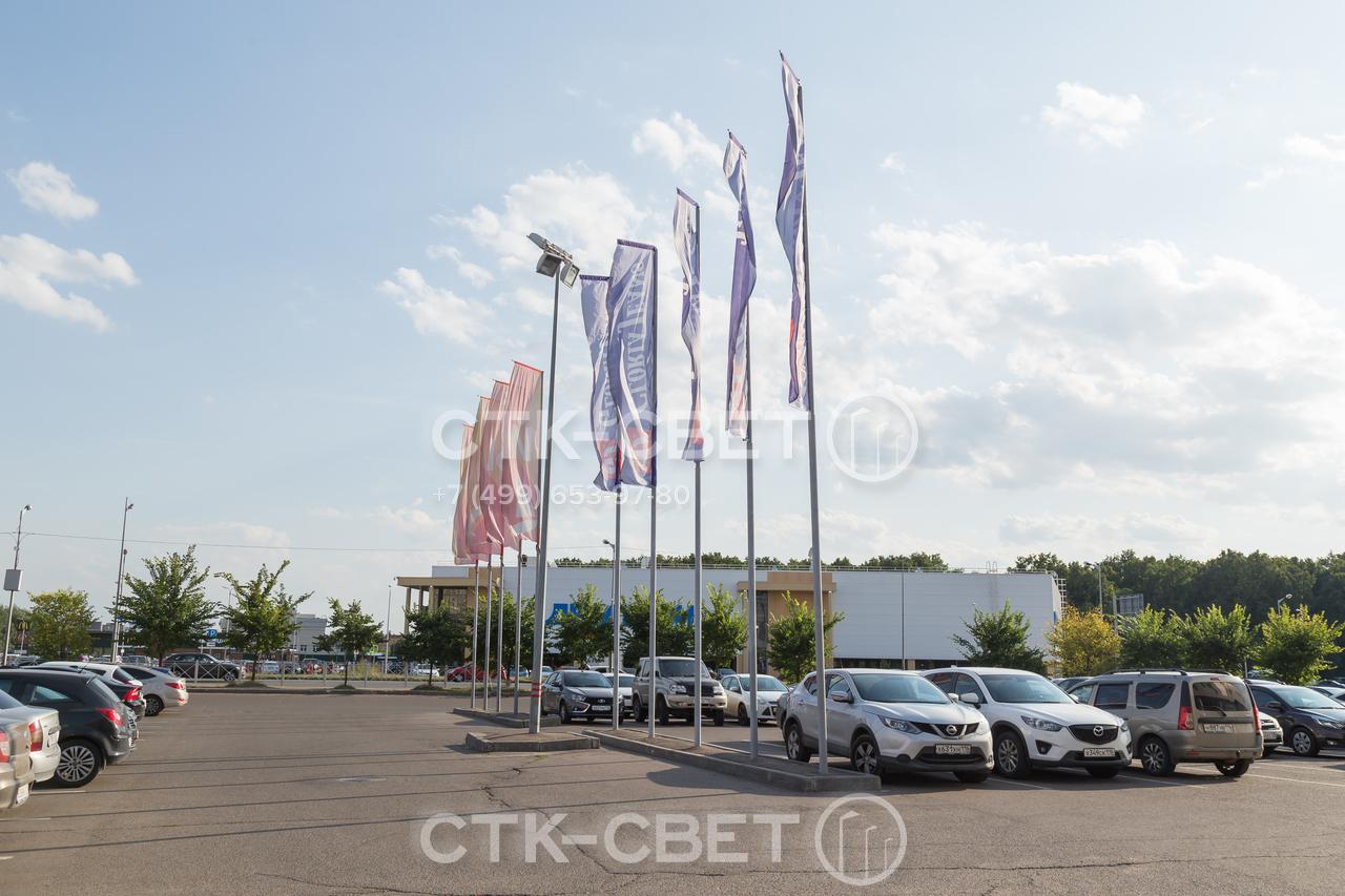 На фото представлены флагштоки, которые используются для украшения парковки перед торговым центром. Флаги и баннеры, размещенные на них, привлекают внимание клиентов и увеличивают рентабельность работы.