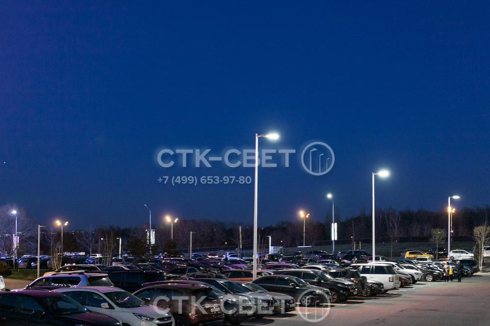 На фото представлены круглоконические опоры несилового типа, которые используются для освещения парковки. На их оголовках установлены кронштейны с минимальными выносами, чтобы световое пятно разместить рядом со стволом.