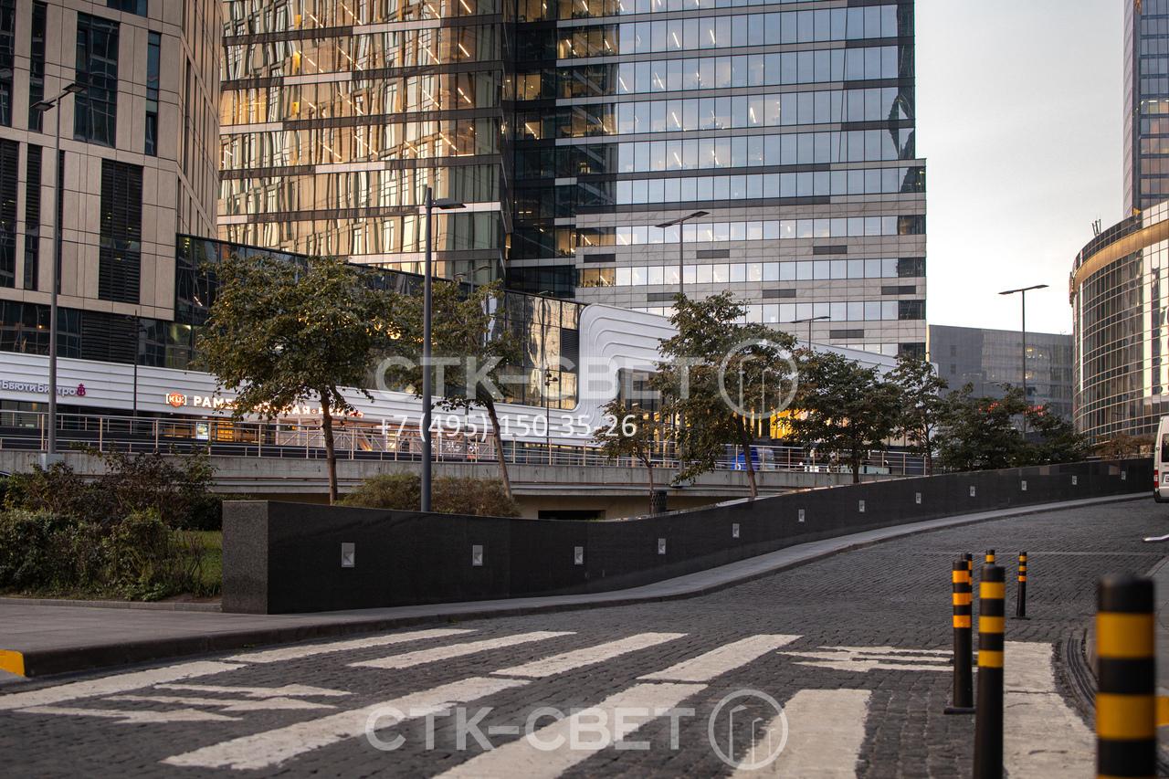На фото представлен пример использования опор НФК для освещения территории бизнес-центра. Для придания конструкциям красивого внешнего вида их поверхность окрашена, использованы светодиодные светильники в необычном корпусе.