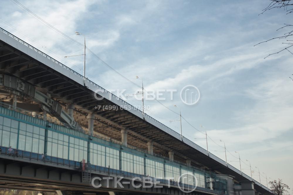 На фото изображены фланцевые стальные граненые опоры, которые применяются для освещения мостов. Особенность фланцевой модели в том, что ее можно установить на закладные элементы без использования фундамента.