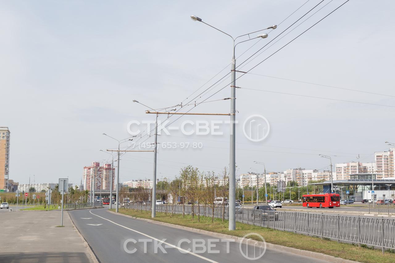 Опоры на фото используются для удержания контактной сети троллейбусов. Два светильника с одной стороны ярко освещают магистраль общего пользования, а один с противоположной стороны – служебную дорогу для электротранспорта.