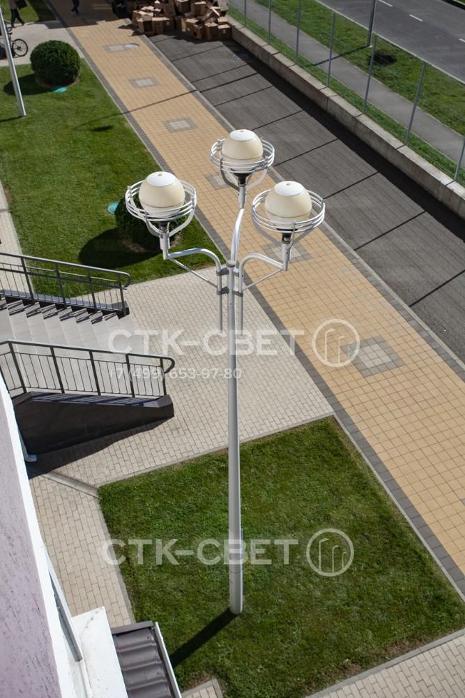 Опора со стволом круглого сечения на фото используется как украшение пространства перед входной группой. На ее оголовке установлены три светильника с веретенообразными отражателями.