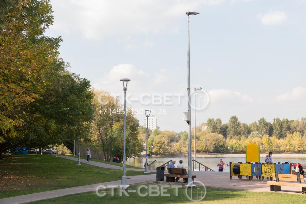 Складные опоры со светодиодными светильниками на фото используются для освещения парка. Такое инженерное решение применяется для того, чтобы автомобильные гидроподъемники не портили дорожки и газоны в парках.