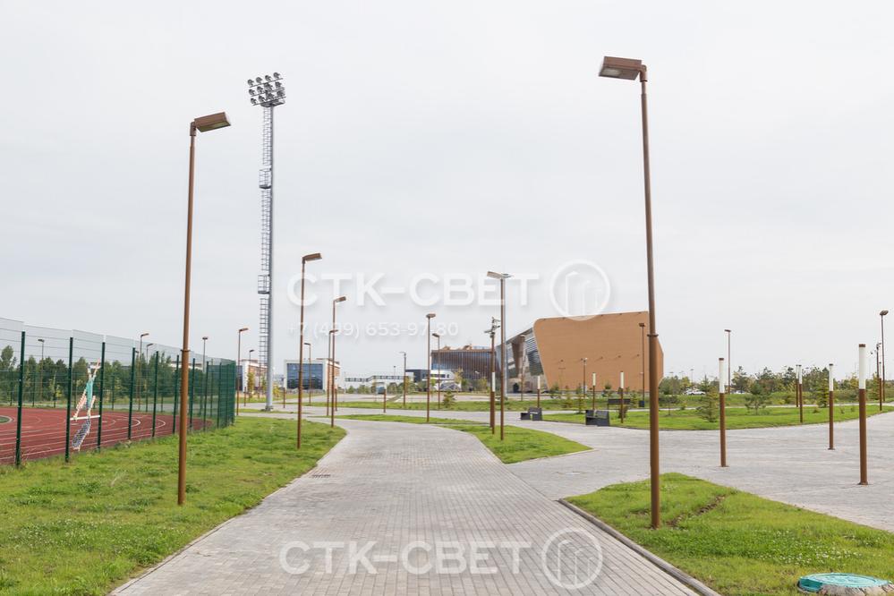 Складные трубчатые опоры на фото используются для освещения пешеходных дорожек в сквере перед спортивным комплексом. Обратите внимание, что благодаря круглому поперечному сечению они красиво смотрятся на фоне другой инфраструктуры.