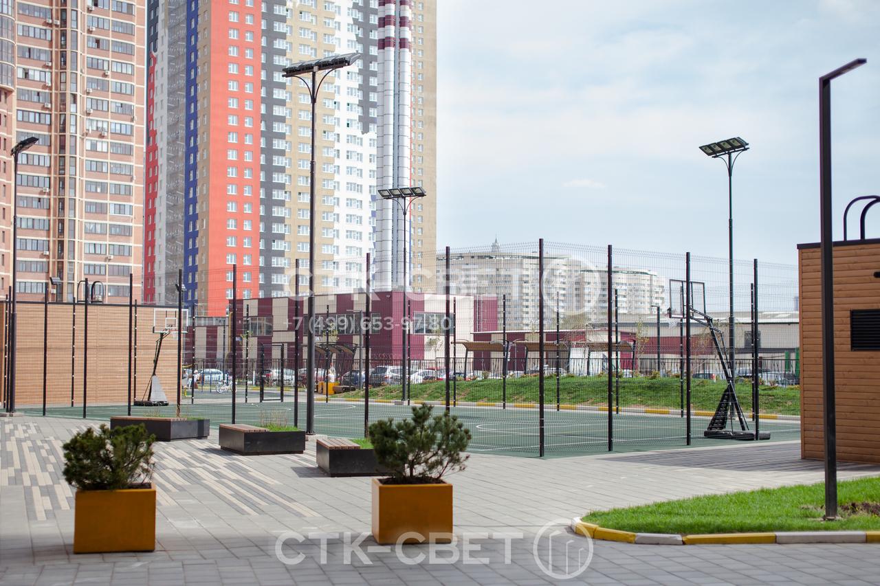 Трубчатые опоры на фото используются для освещения спортивной площадки. Поверхность опор окрашена в черный цвет для улучшения внешнего вида, на оголовке закреплены прожекторы направленного света.