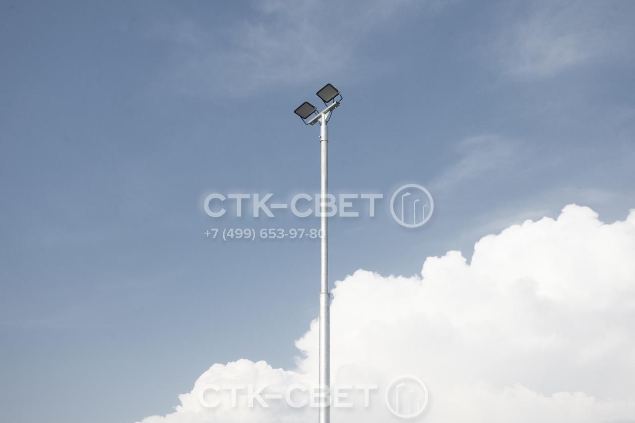 Представленная на фото трубчатая опора изготавливается из стальных труб разного диаметра. На стандартный оголовок могут устанавливаться различные приборы освещения – светильники заливающего света или прожекторы.