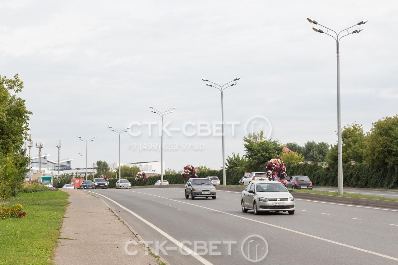Изображенные на фото силовые опоры используются для освещения двух противоположных полос движения на автомобильной дороге. Подземное подключение проводов увеличивает надежность инженерной системы.
