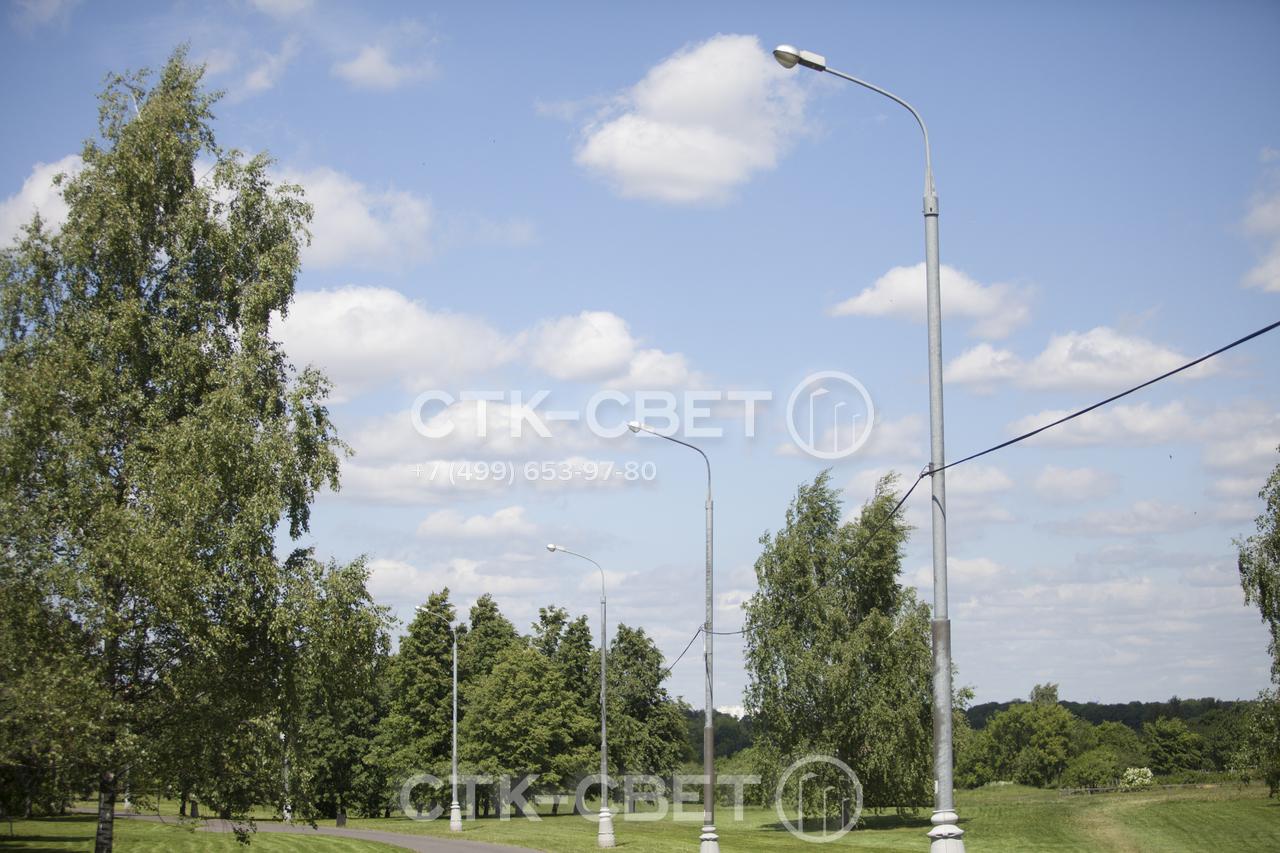 На фото представлены трубчатые опоры, которые используются для освещения парка. Они имеют большую высоту и мощные светильники, чтобы освещать большую площадь. Благодаря круглому сечению лучше смотрятся на фоне растительности.
