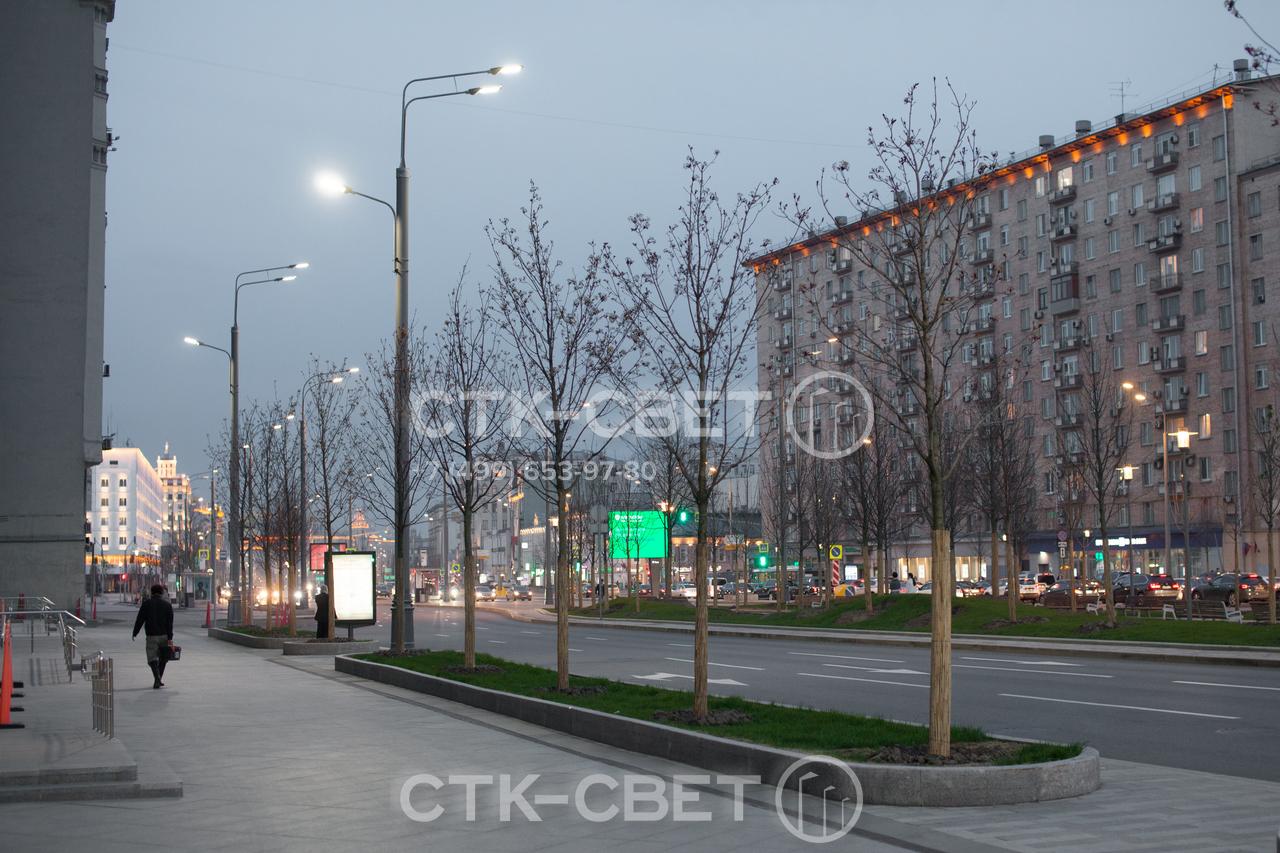 В представленном на фото примере трубчатые опоры используются одновременно для освещения проезжей части и тротуара. Над проезжей частью установлены два светильника, над тротуаром – один на дополнительном кронштейне.