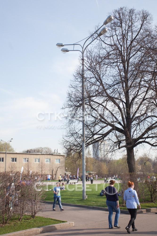 Силовая опора трубчатого типа устанавливается в парках и скверах в случае, когда нужно закрепить на ней большое количество светильников. В примере на фото на одном стволе установлено сразу 4 световых прибора на длинных выносах.