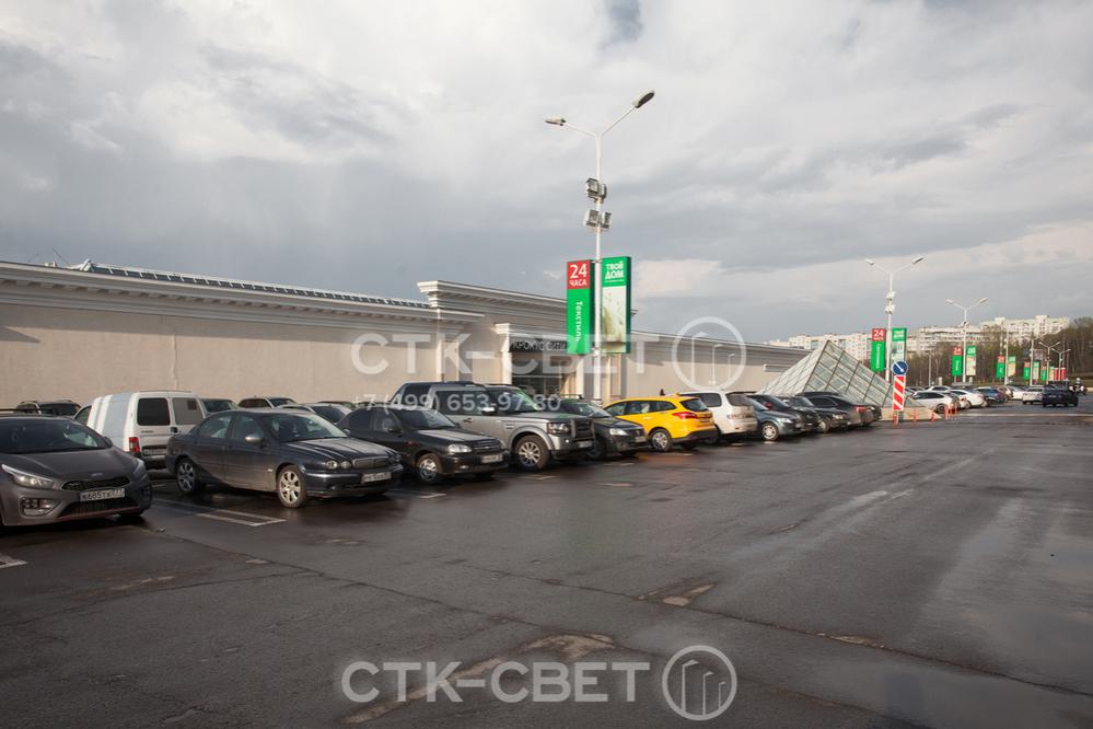 На фото приведен пример использования трубчатой силовой опоры для освещения парковки перед торговым центром. На стволе, помимо светильников, закреплены прожекторы направленного света и световые боксы.
