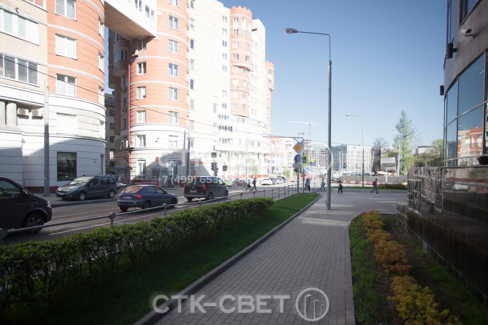 Прямостоечная трубчатая опора установлена на тротуаре рядом с жилым домом. Особенность такого способа монтажа в том, что мостить плитку можно вплотную к стволу. Поэтому ствол конструкции не мешает движению людей.