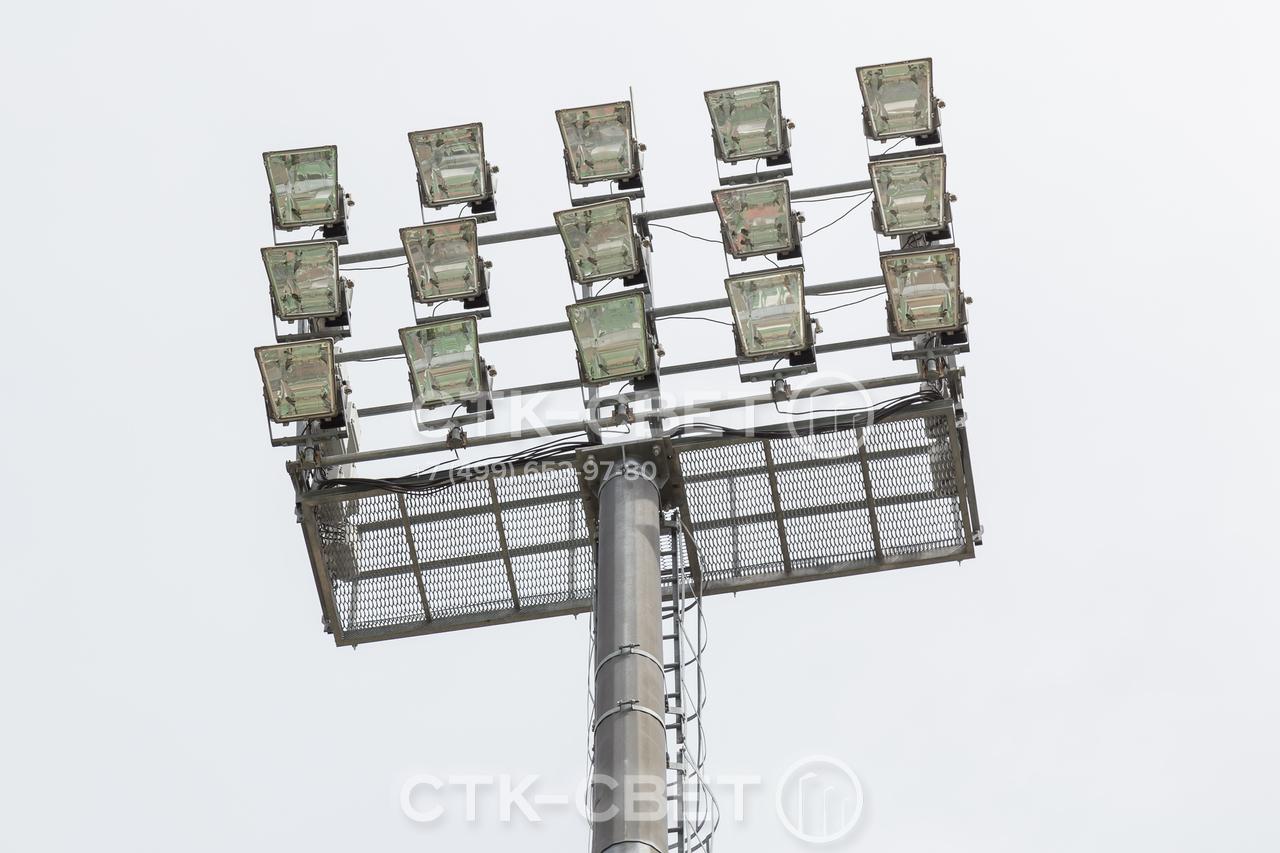 На фото изображена рама для прожекторов в верхней части мачты, а также технологическая площадка для персонала. К стволу прикреплена лестница, которая позволяет электрику подняться на площадку.