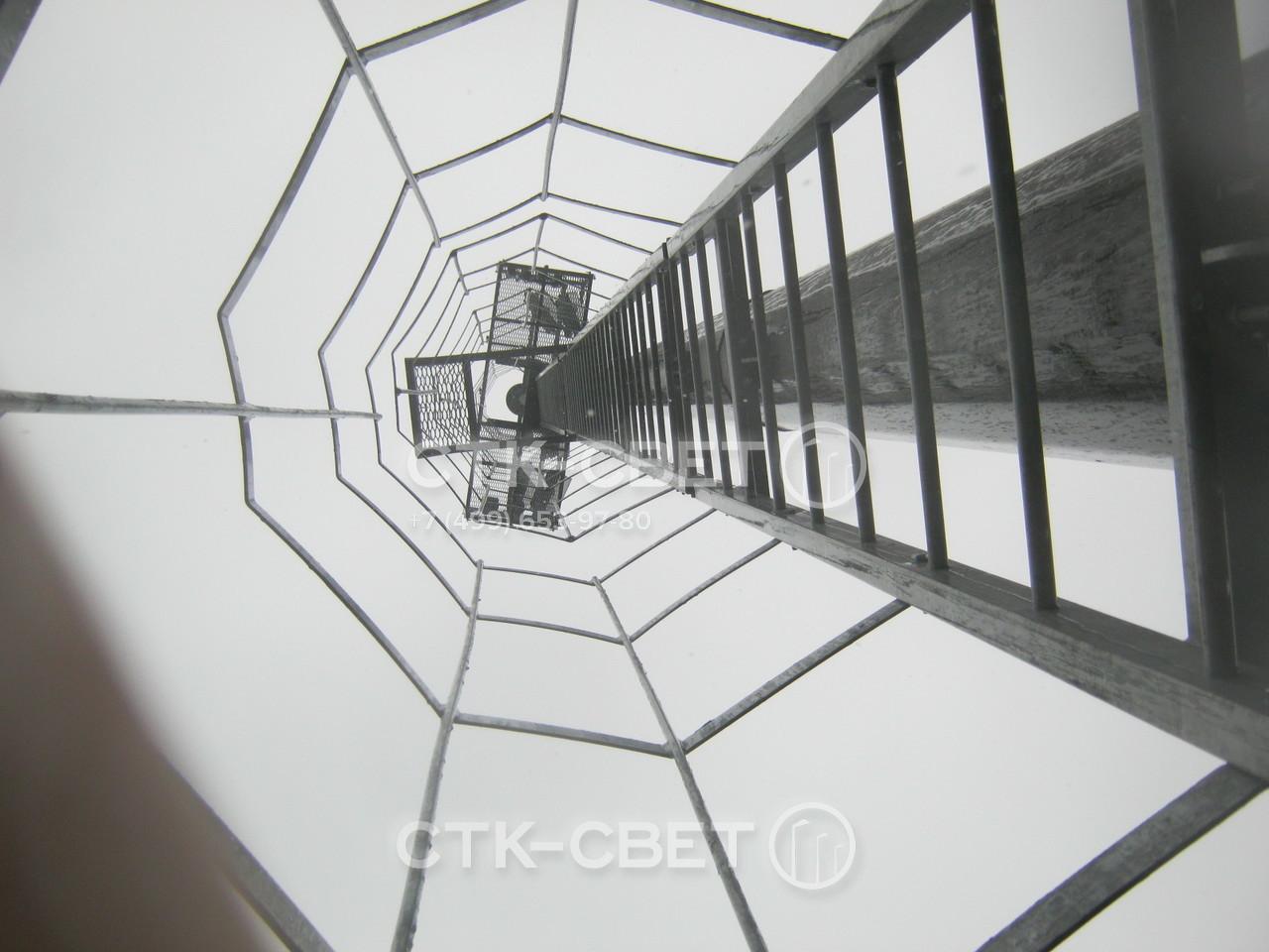 Лестница с защитной рамой уменьшает затраты на эксплуатацию инженерной конструкции. Для обслуживания светильников не нужно арендовать автомобильный гидроподъемник. Электрик поднимается по лестнице.