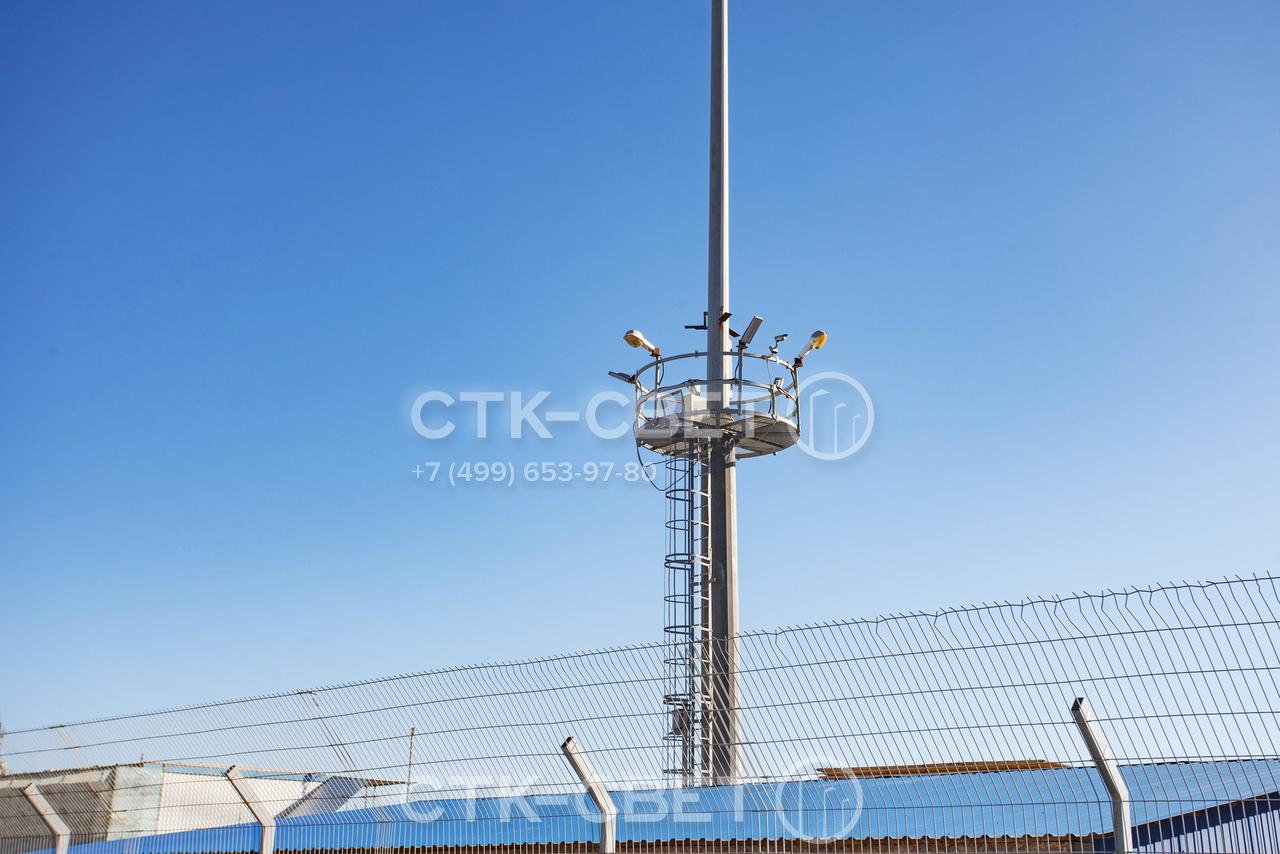 На фото представлена мачта МГФ-СР-М, которая используется для освещения территории порта. Обратите внимание, что на ограждении нижней стационарной площадки установлены приборы освещения и громкоговорители системы оповещения.