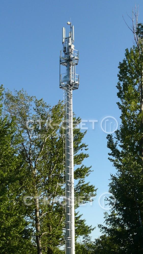 На фото представлена мачта связи с двумя технологическими площадками. На них находится электрик или инженер, обслуживающий оборудование связи. Подъем на верхушку производится по лестнице с предохранительной рамой.