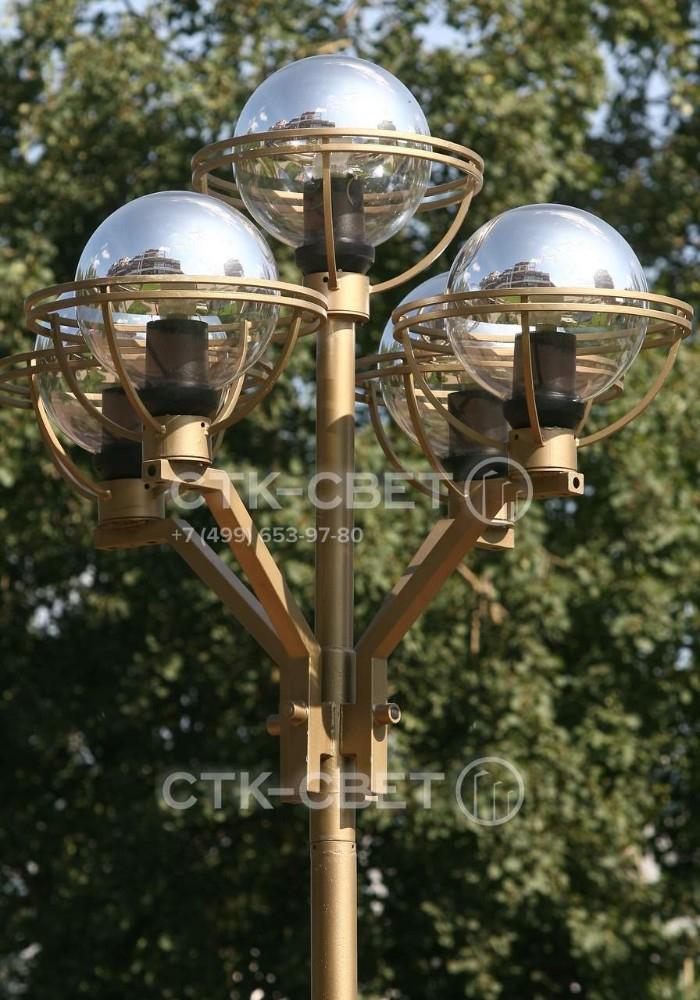 Пример использования опоры Бол для создания заливающего освещения. На оголовок установлен кронштейн под пять светильников с шарообразными отражателями. Вся конструкция окрашена в золотистый цвет.